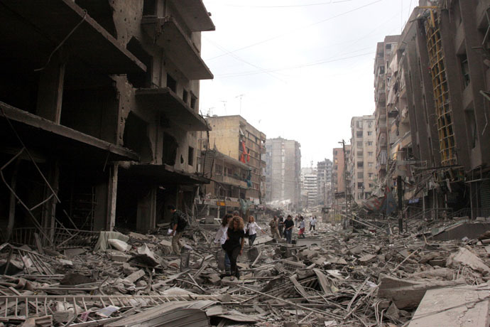 Journalist inspect the damaged buildings after Israeli air raids in southern Beirut July 20 2006