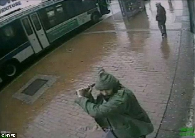 Act of terror? Suspect Zale Thompson can be seen swinging a hatchet towards police officers at 2 p.m. on Thursday afternoon in Jamaica, Queens