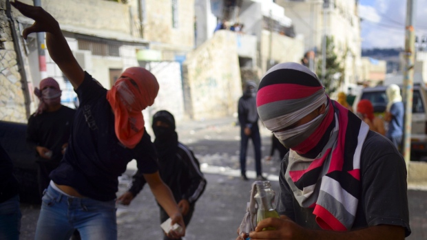 Palestinian youths throw stones during clashes with Israeli border police after Moatez Higazi, a man suspected of trying to kill a hard-line Jewish activist in Jerusalem, was shot in east Jerusalem on Oct. 30, 2014