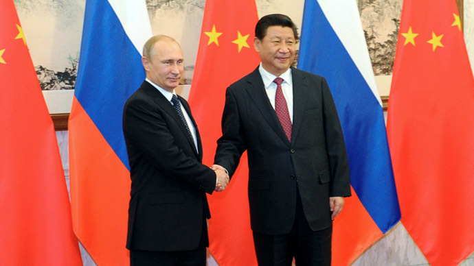 Russia's President Vladimir Putin shakes hands with his China's counterpart Xi Jinping