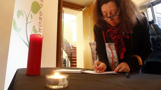 A member of the public signs a book of condolence at St Georges Tron Church in Glasgow