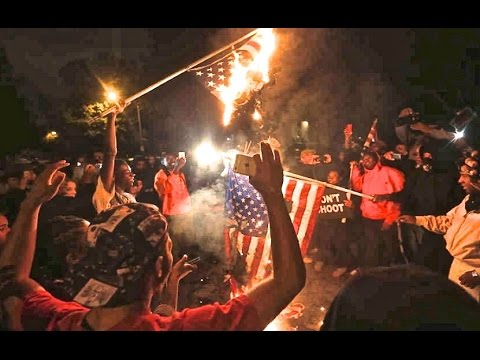 'Don't Shoot' T-Shirt in the background as Americans burn their own flag