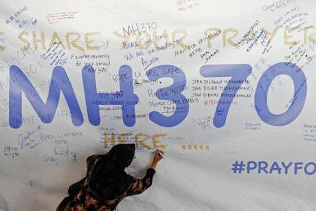 A woman writes a message of support and hope for passengers of the missing Malaysia Airlines MH370