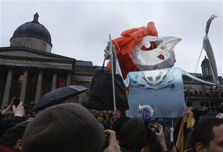 A puppet made to represent the late former British PM Thatcher is carried through crowd at a party in Trafalgar Square to celebrate her death in London