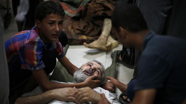Palestinian boy comforts his father, whom medics said was wounded by Israeli shelling in Shejaia, at a hospital in Gaza City